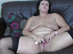 Fat brunette fro saggy tits is wearing jet-black stockings while masturbating like crazy, on the couch